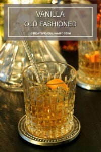 Vanilla Old Fashioned Cocktail with Orange Peel Garnish in Front of Glass Decanter