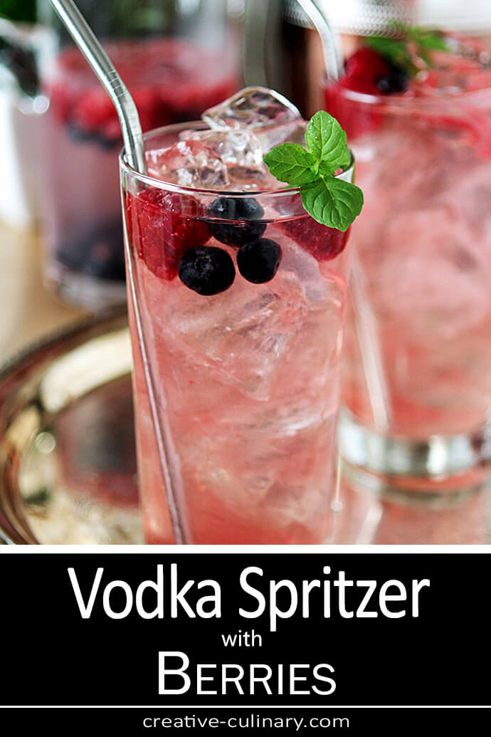 Vodka Spritzer Cocktail with Mixed Berries served in a tall glass with raspberry, blueberry and mint garnish.