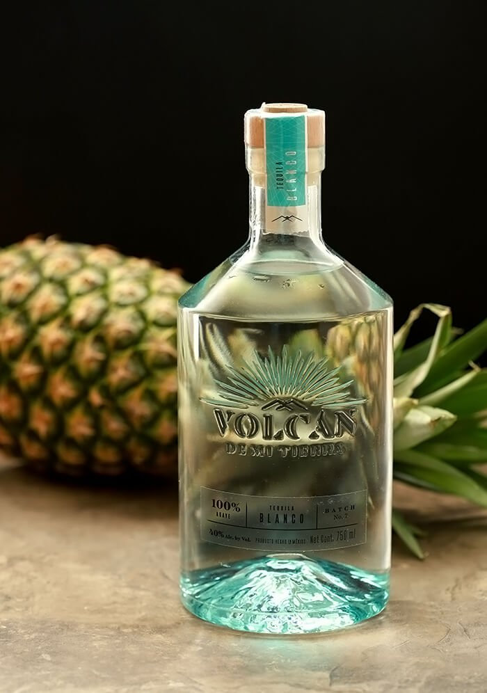 Bottle of Volcan Tequila Staged in front of horizontal pineapple