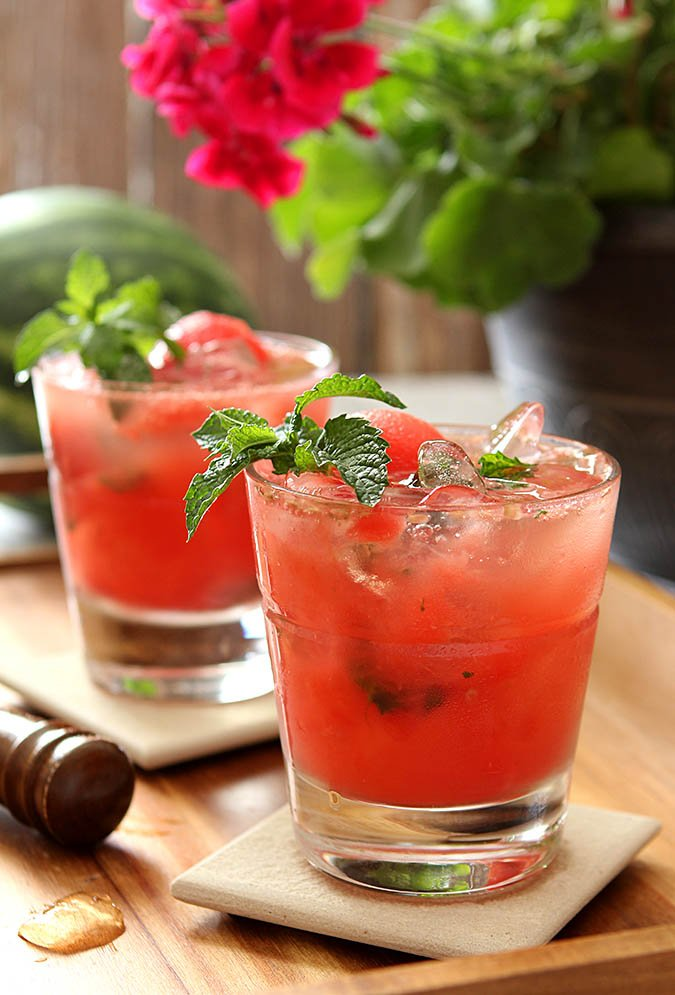 Watermelon Mint Mojito Cocktails served on coasters in an outdoor setting.