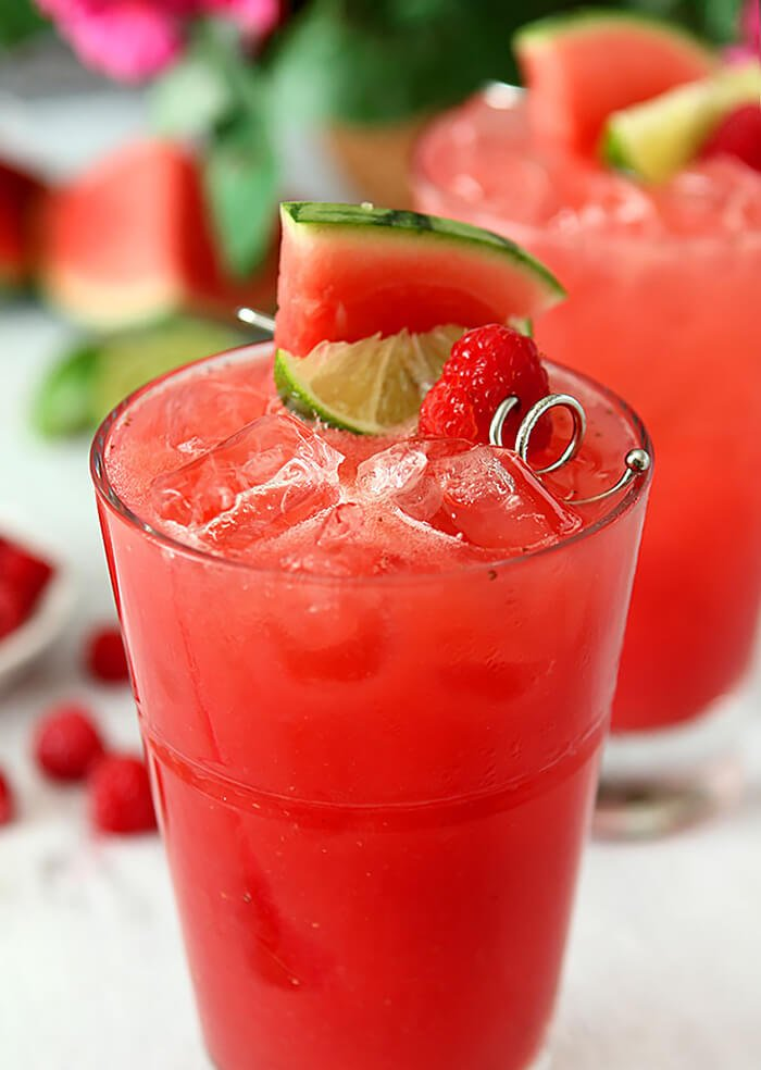 Watermelon Raspberry Cooler Cocktail with Rum Garnished with Watermelon, Raspberry and Lime Wedges