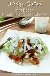 Iceberg Wedge Salad with Bacon, Croutons, and Blue Cheese Dressing on a White Plate