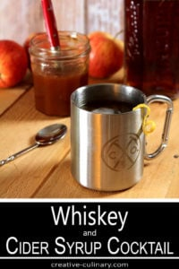 Whiskey and Cider Syrup Cocktail in a Tin Cup with Lemon Twist with Cider Syrup in Background