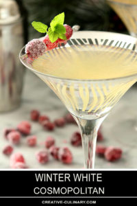 Closeup of Winter White Cosmopolitan Cocktail Served in a Martini Glass Garnished with Sugared Cranberries